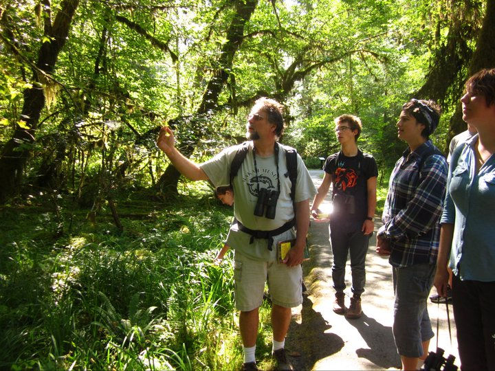 professor and students in the green forest examining a treel