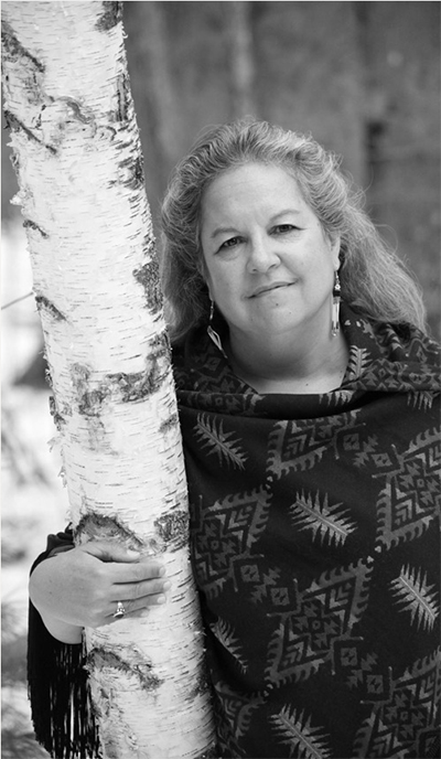 On a chilly fall morning a thoughtful looking person leans agaisnt a birch tree in the woods