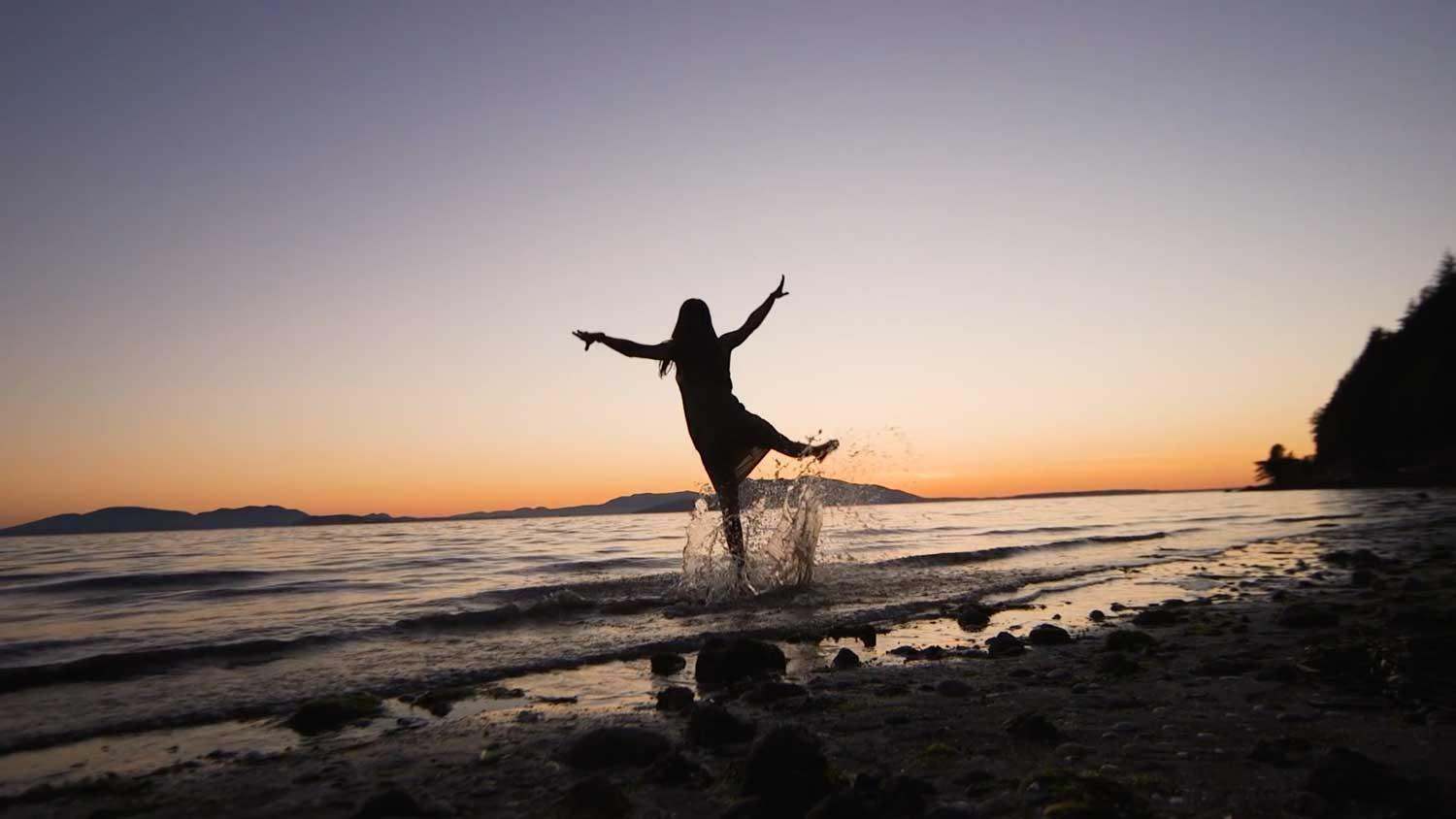 A woman stands on a beach, arms outstretched, playing in the surf during sunset
